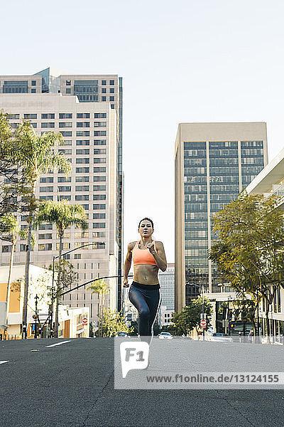 Full length of determined female athlete running on city street