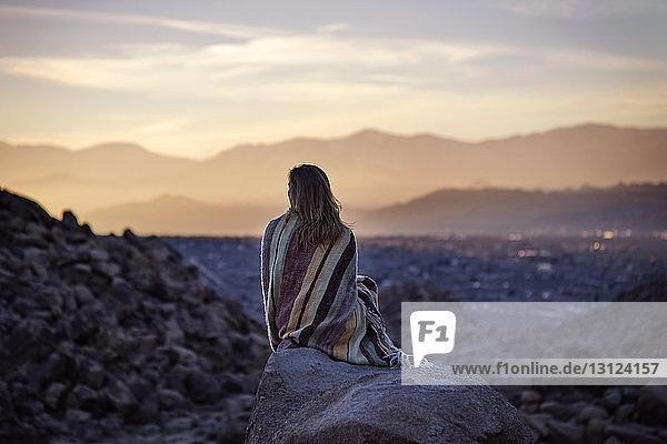 Rückansicht einer in eine Decke gehüllten Frau  die auf einem Felsen gegen den Himmel sitzt