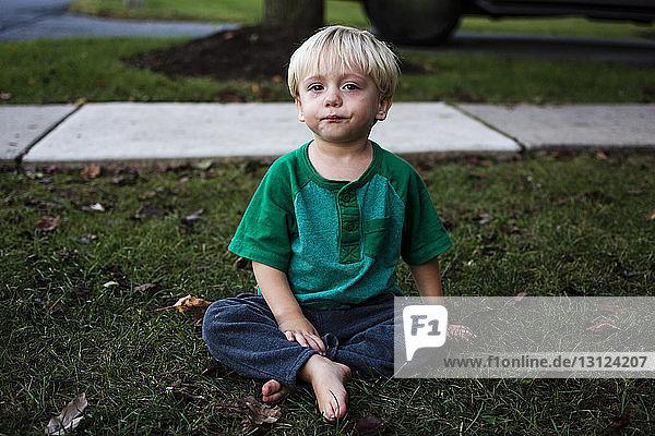 Porträt eines weinenden Jungen  der im Hinterhof sitzt