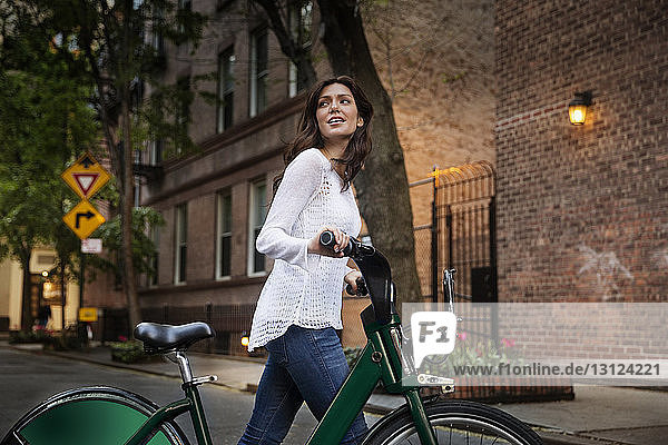 Young woman walking with bicycle on street