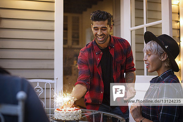 Man placing cake on table for surprised woman