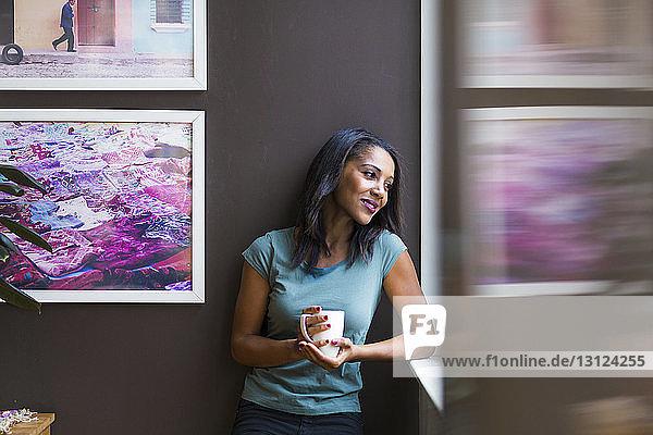 Nachdenkliche Frau hält Kaffeetasse in der Hand  während sie zu Hause an Bilderrahmen an der Wand steht