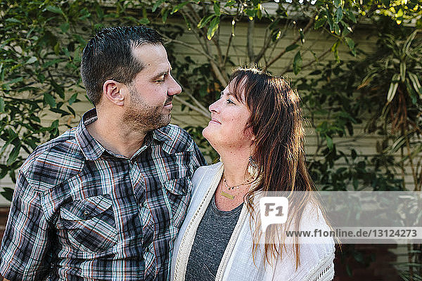 Close-up of romantic couple looking at each other while standing against wall in yard