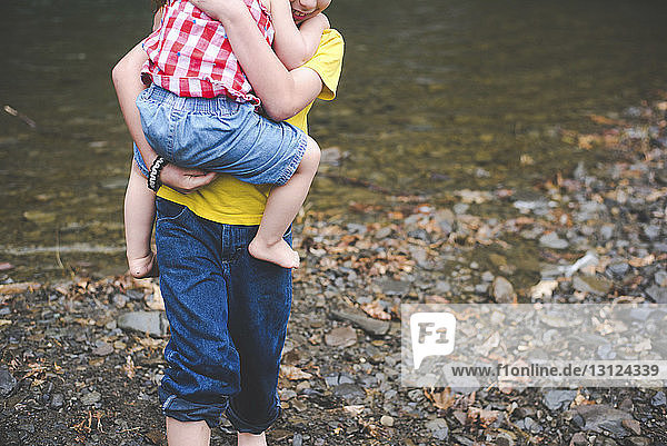 Midsection of brother carrying sister while standing at lakeshore