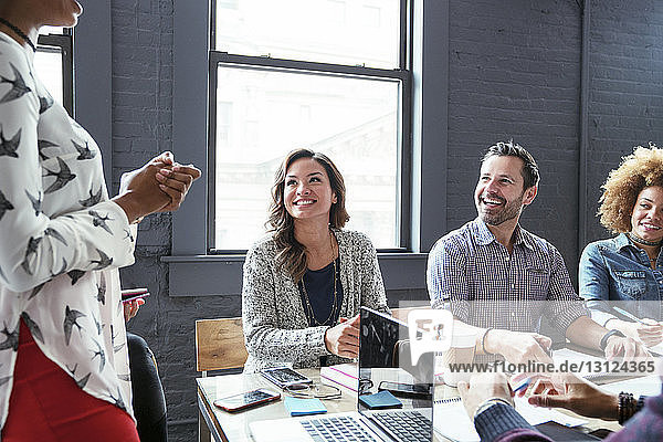 Midsection of businesswoman explaining colleagues in meeting room