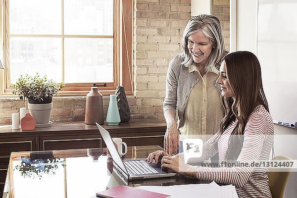 Happy mature businesswoman using laptop with female executive in board room