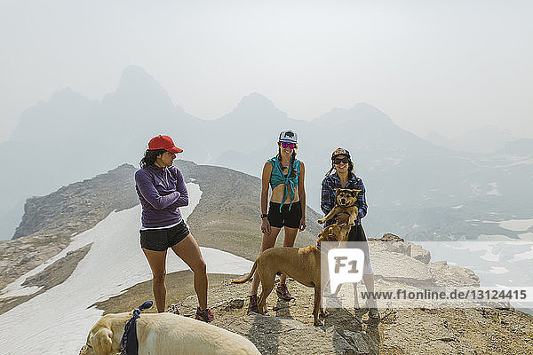 Friends with dogs standing on mountain