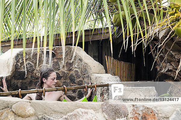 Naked woman bathing under shower