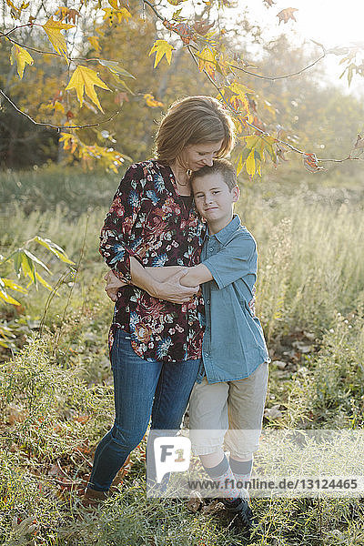 Full length of son embracing mother while standing on field at park
