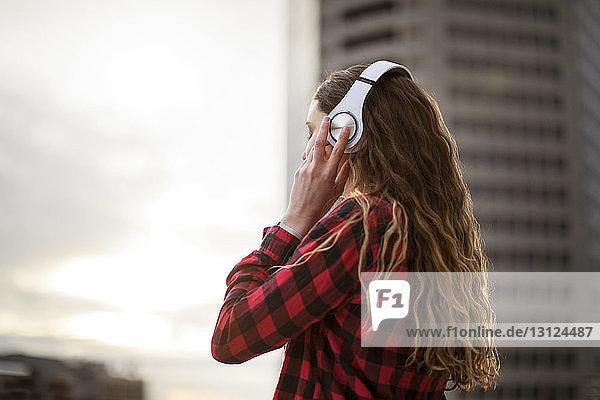 Seitenansicht einer Frau  die Kopfhörer trägt  während sie am Gebäude steht