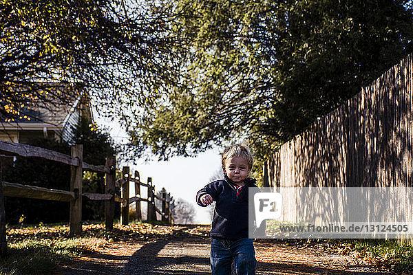 Porträt eines Jungen  der auf einem Fußweg geht
