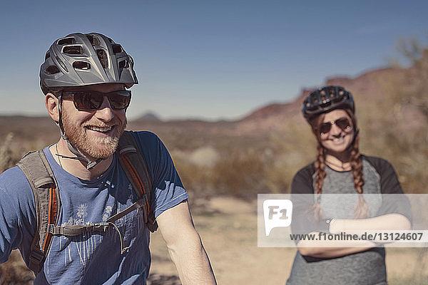 Glückliche männliche und weibliche Mountainbiker stehen am Berg vor strahlend blauem Himmel