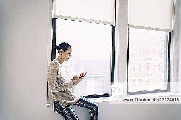 Woman using mobile phone while sitting on window sill at home