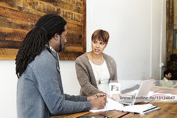 Businesswoman looking at male colleague while working in creative office