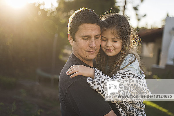 Father and daughter with eyes closed embracing in yard during sunset