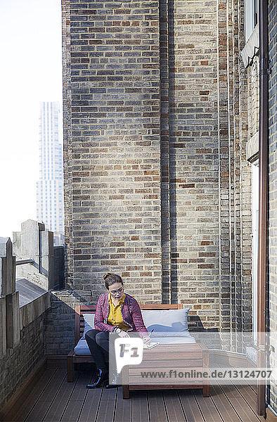 Geschäftsfrau schreibt  während sie auf dem Sofa auf dem Balkon des Büros sitzt
