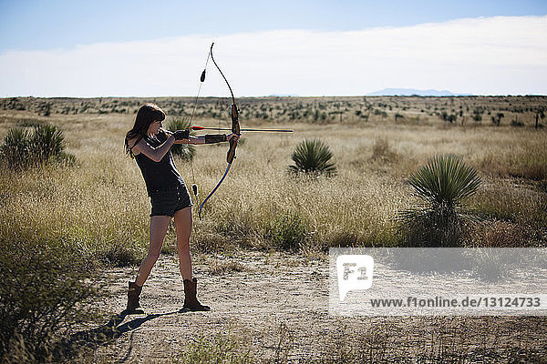 Woman aiming with bow and arrow while standing on field