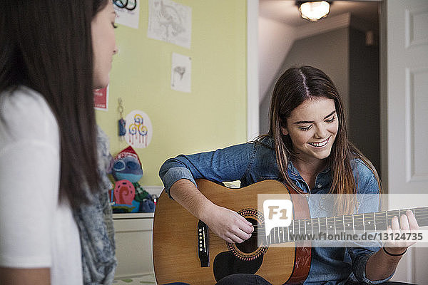 Woman practicing guitar while sitting with sister at home
