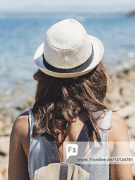 Rückansicht einer Frau mit Rucksack  die an einem sonnigen Tag am Felsstrand steht