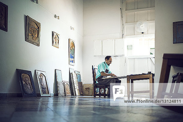 Seitenansicht einer Handwerker-Schnitzerei beim Sitzen in der Werkstatt