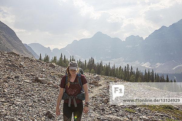 Frau mit Rucksack steht auf Feld im Banff-Nationalpark gegen den Himmel