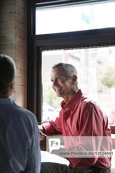Lächelnder Mann sieht Frau an,  während er im Café am Tisch sitzt