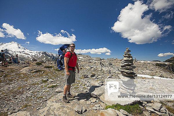 Wanderer trägt seinen Sohn auf dem Rücken  während er im North Cascades National Park an den Bergen steht