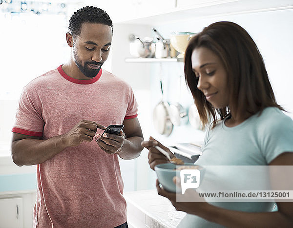 Man using phone while woman having breakfast in kitchen at home