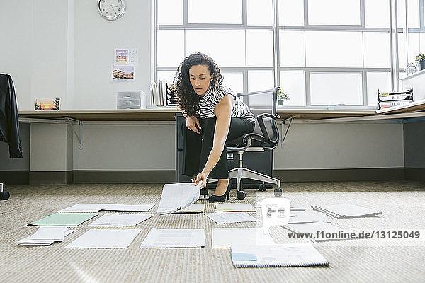 Geschäftsfrau ordnet Dokumente auf dem Boden im Büro an