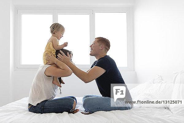 Mutter trägt die Tochter auf den Schultern  während sie zu Hause mit dem Vater im Bett spielt