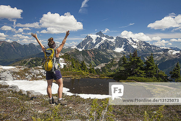 Rear view of female hiker with backpack standing at North Cascades National Park