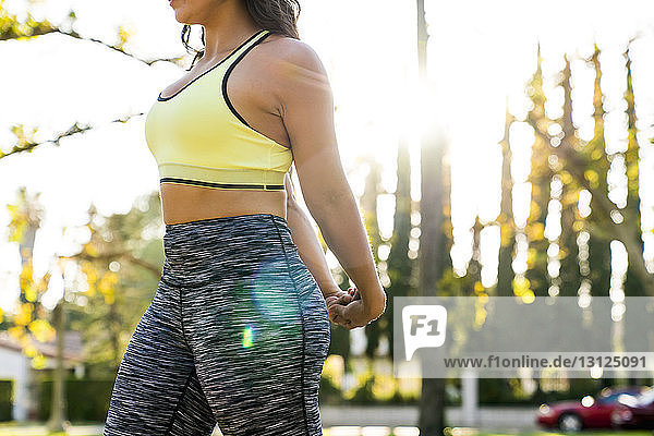 Midsection of woman stretching arms behind back while exercising in park