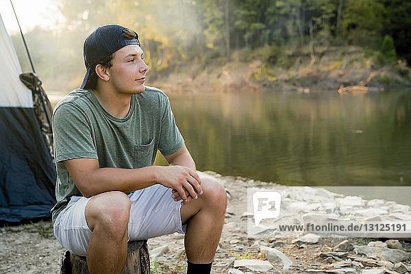 Junger Mann schaut weg  während er am See auf dem Campingplatz sitzt