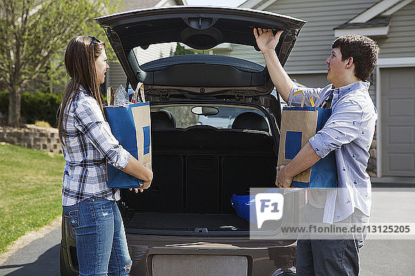 Siblings holding bags and standing by car trunk on road