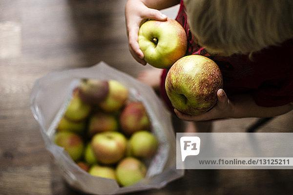 Hochwinkelaufnahme eines Jungen  der zu Hause Äpfel hält