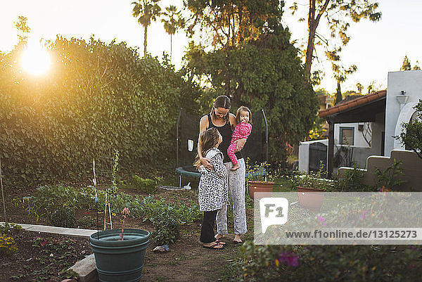 Mother with daughters standing in yard against sky during sunset