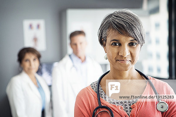 Portrait of confident female doctor in clinic with colleagues standing in background