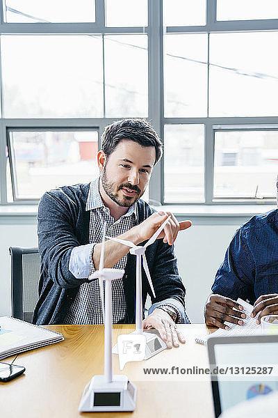 Geschäftsmann berührt Windturbinenmodell während einer Besprechung im Büro