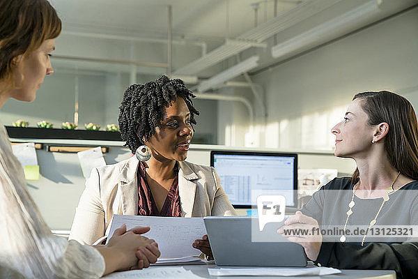 Geschäftsfrauen diskutieren im Büro am Tablet-Computer