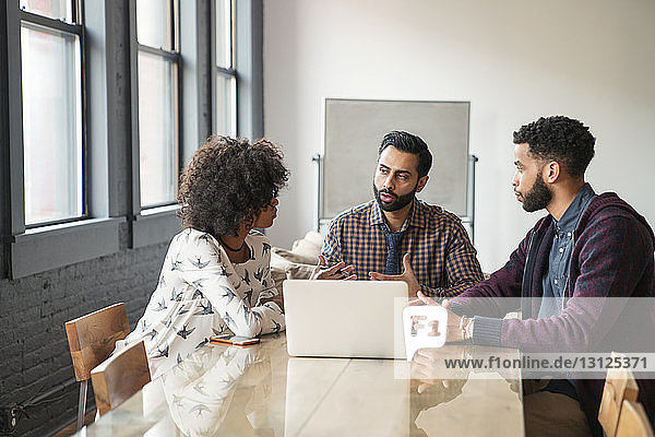 Business people discussing while sitting at desk in office