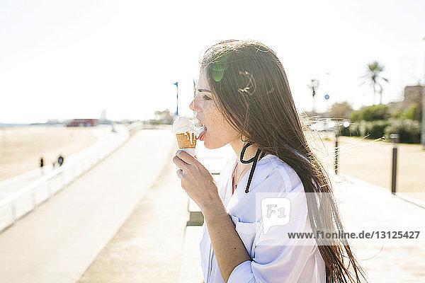 Seitenansicht einer jungen Frau  die Eiscreme leckt  während sie am Strand vor klarem Himmel steht