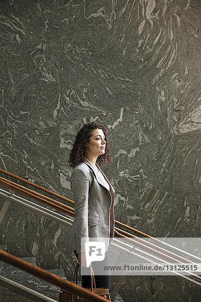 Seitenansicht einer nachdenklichen Geschäftsfrau  die auf Stufen in einem modernen Gebäude steht
