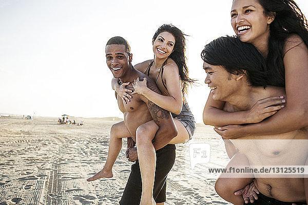 Glückliche Freunde genießen Huckepack-Fahrten am Strand