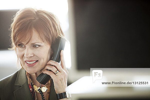 Close-up of mature businesswoman using phone at office