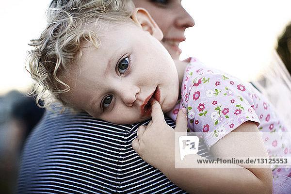 Porträt eines niedlichen Mädchens mit dem Finger im Mund  das von der Mutter ins Freie getragen wird