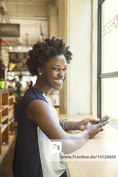 Portrait of happy woman holding smart phone in store