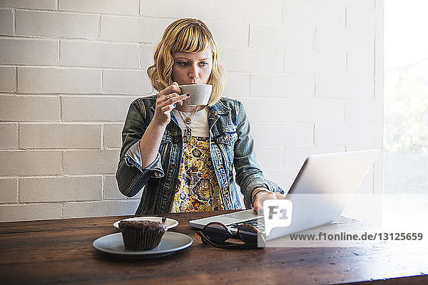 Woman drinking coffee while using laptop computer in cafe