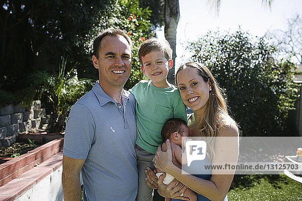 Porträt von glücklichen Eltern mit Kindern im Hof stehend