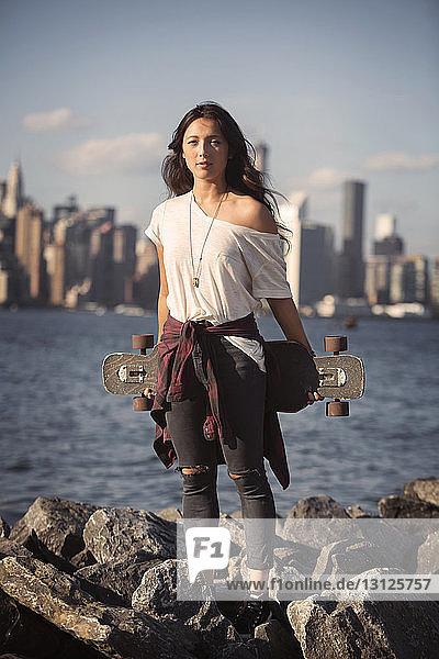 Porträt einer Frau  die ein Skateboard auf einer felsigen Küste gegen den Himmel hält