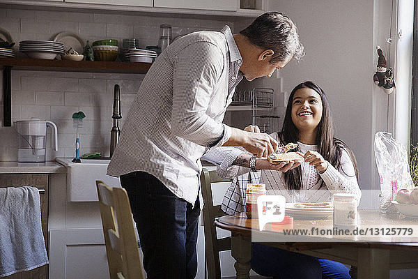 Smiling girl looking at father applying peanut butter on bread in kitchen